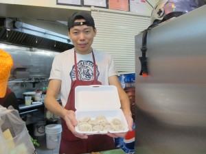 Man holding tray of dumplings.
